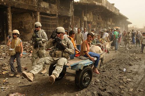 イラク・バグダッドでイラク人の少年の荷車に乗っかるアメリカ兵。2008年5月31日撮影。アメリカ空軍提供。.jpg