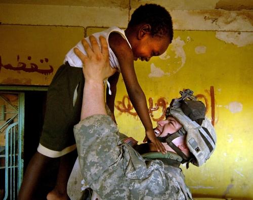 ハート・ロッカー↑イラク人の少年と遊ぶ兵士。その間、少年の母は人口調査に応じていた。アメリカ空軍提供。.jpg